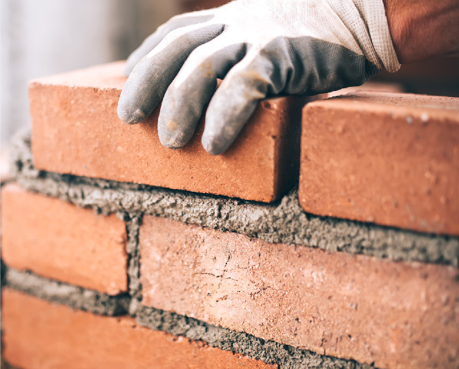 Construction worker's hands laying bricks.