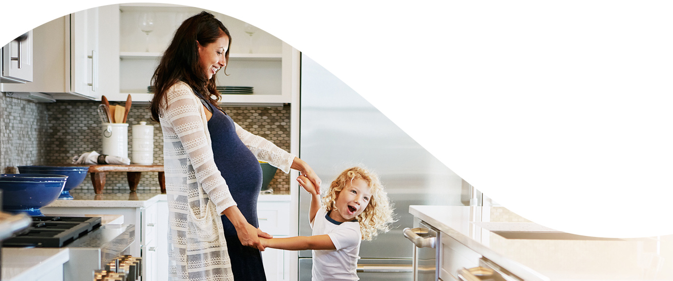 Mother and child smiling and dancing in a modern kitchen.
