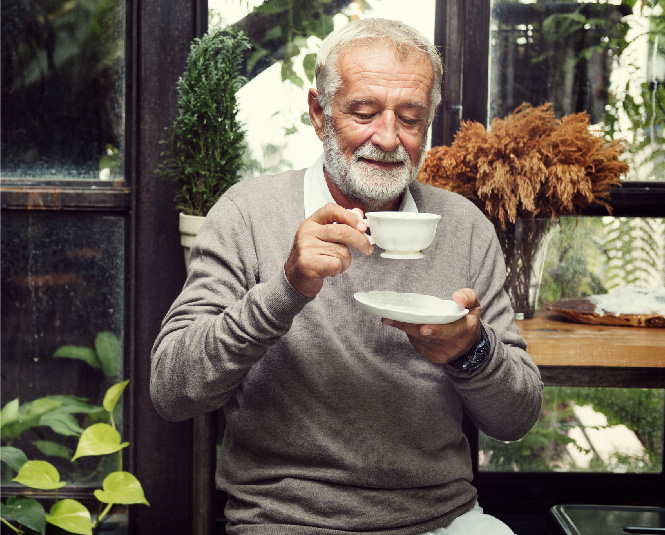 Older gentleman enjoying a hot drink surrounded by greenery.