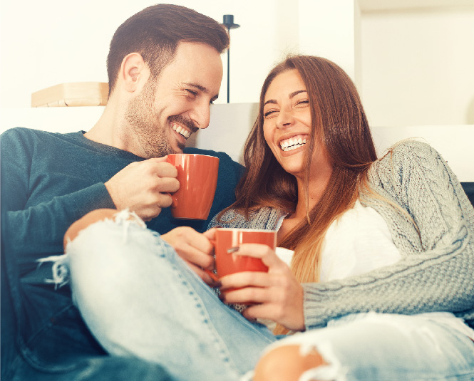 Young couple on a couch smiling and holding coffee mugs.