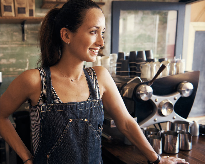 Young female business owner smiling in a coffee shop.