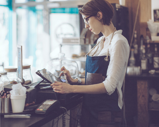A young woman using a point of sale system in a coffee shop.