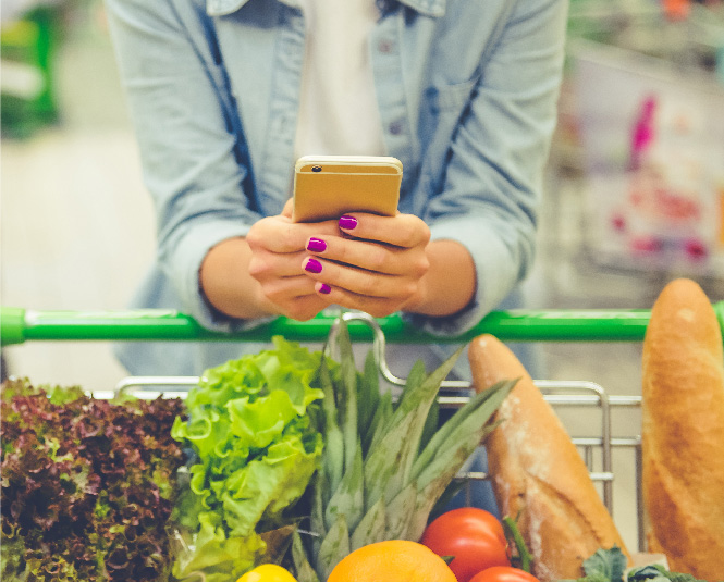 Young woman with a grocery cart full of produce holding her phone.